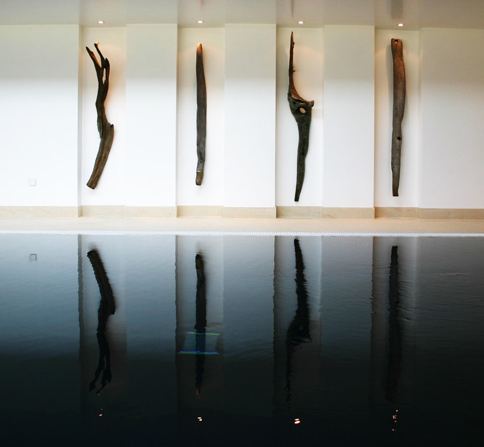 Sculptures reflection into black-tiled pool.
